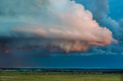 Pink clouds over the meadow. Curly cloud drops rain on the green meadow Stock Image
