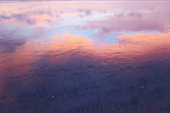 Pink clouds reflection in wet sand of Kuta beach, Bali Royalty Free Stock Photos