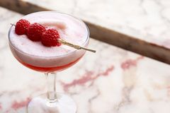 Pink Clover Club Cocktail Drink with Raspberry Garnish. A Clover Club cocktail, originating in a restaurant of the same name in Philadelphia in the late 1800s stock image