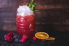 Pink cocktail with lemon in a glass. Lemon slices lie near the glass. Raspberry cocktail with ice and mint is on the table. Ice cubes and raspberries lie stock photo