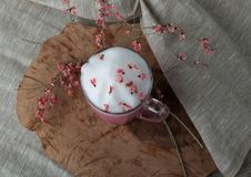 Pink coffee latte macchiato in a glass cup on a wooden backing decorated with dried flower. S with air foam stock images