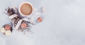 Pink coffee mug with sweet pastel french macaroons and wil. Low on light table from above. Breakfast on Mothers day or Women`s day. Tender spring background royalty free stock images