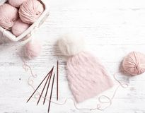 Pink coil of yarn in the basket and knitting needles. Royalty Free Stock Images