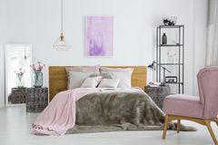 Pink accessories in white bedroom. Pink color accessories in bright white bedroom with king-size bed and armchair Royalty Free Stock Photos