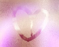 Pink color blurred lovely heart symbol drawn by hand on the wet rainy glass. Valentines day.  Royalty Free Stock Photos
