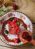 Pink color cocktail on rustic surface garnished with berries and. Pink color cocktail on a vintage plate garnished with raspberries and blackberries Royalty Free Stock Photos