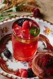 Pink color cocktail on rustic surface garnished with berries and. Pink color cocktail on a vintage plate garnished with raspberries and blackberries Royalty Free Stock Image