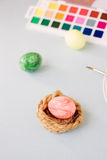Pink color egg on bright background. Nest and easter. Royalty Free Stock Images