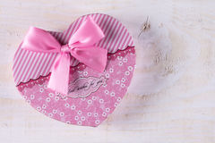 Pink color heart shaped box with pink bow above wooden background.  Stock Photography
