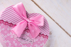 Pink color heart shaped box with pink bow above wooden background.  Royalty Free Stock Image