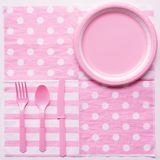 Pink color paper plate with plastic spoon, fork and knife royalty free stock image