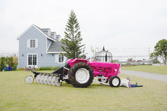 Pink color tractor in the farm Royalty Free Stock Photo
