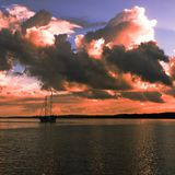 Pink colored cumulonimbus cloud, sunset seascape. Summer sunset with predominately cumulonimbus clouds against a steel blue sky reflected in ocean water. Fraser royalty free stock images
