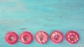 Pink colored donuts. On a blue wooden background royalty free stock photography