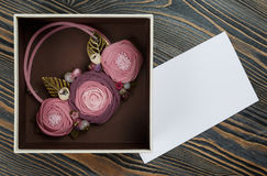 Pink-colored handmade necklace putted in a box and a letter of congratulations are lying on wooden background Royalty Free Stock Image