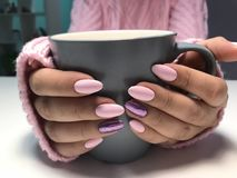Warm evening tea cup hugged by hands with interesting cute manicure. Pink colored nails hugging a coffee cup in pink knitted sweater, Christmas, warm, warmness stock photography