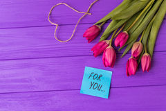 Pink colorful tulips over a purple background, in a flat lay composition with heart and inscription on paper for you. Present concept Stock Photography