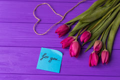 Pink colorful tulips over a purple background, in a flat lay composition with heart and inscription on paper for you. Present concept Royalty Free Stock Image