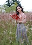 Happy Asian Chinese woman girl feel freedom sweet dream pray flower field autumn fall park grass lawn hope nature read book school. Pink colour grass lawn, rose stock images