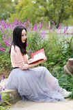 Happy Asian Chinese woman girl dream sit pray flower field autumn fall park lawn hope nature read book knowledge freedom carefree stock images