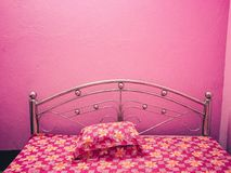 Pink coloured bed with floral bed sheet with pink walls. Pink coloured bed with pink walls in a hotel with silver handles of the bed and a colourful floral bed royalty free stock photography