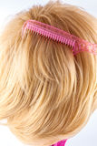 Pink comb in blonde wig Stock Photo