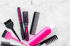 Pink combs, brushes and spray for hairdresser work on stone desk background top view mockup Royalty Free Stock Photos