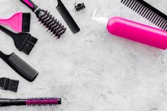 Pink combs, brushes and spray for hairdresser work on stone desk background top view mockup Royalty Free Stock Photography