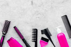 Pink combs, brushes and spray for hairdresser work on stone desk background top view mockup Stock Images