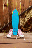 Pink converse sneakers near blue skate which stands near wooden. Pink converse sneakers with untied laces on a wooden floor near blue penny skate board longboard Royalty Free Stock Photos