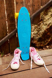 Pink converse sneakers near blue skate which stands near wooden Royalty Free Stock Photography