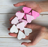 Pink cookies in woman hands. Heart shape, white background Stock Photography