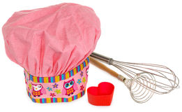 Pink cooking hat, with multi-colored pattern, hearts, flowers and owls. Hearts molds for cookies in red. Whisk to froth Stock Photo