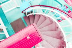 Pink coral and green pastel modern spiral staircase descent royalty free stock photos