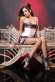 Pink corset and fishnet stockings. Cute brunette in pink corset on a vintage chair royalty free stock photo