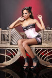 Pink corset and fishnet stockings. Cute brunette in pink corset on a vintage chair stock photo