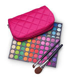 Pink cosmetic bag and palettes of colored eyeshadow for makeup with brushes royalty free stock photo