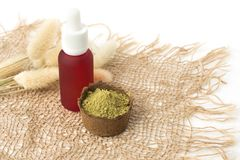 Pink cosmetic bottle and henna powder for dyeing hair, eyebrows and mehendi on a burlap made of natural material stock images