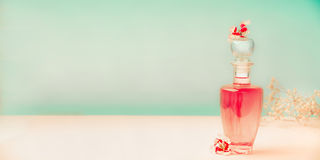 Pink Cosmetic bottle with skin care product or perfume with flowers Stands on the table at turquoise background, front view, banne royalty free stock images