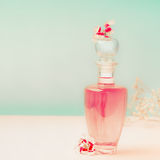Pink Cosmetic bottle with skin care product or perfume with flowers Stands on the table at turquoise background, front view royalty free stock photo
