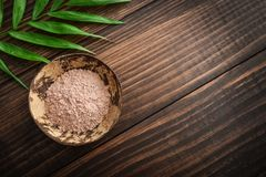 Pink cosmetic clay. In coconut bowl on wooden background top view Royalty Free Stock Photography