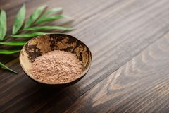 Pink cosmetic clay. In coconut bowl on wooden background closeup Royalty Free Stock Photography