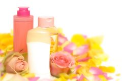 Pink cosmetics. Cosmetics with pink and yellow roses and petals royalty free stock image