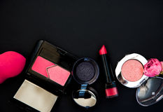 Pink cosmetics on a black background. Background with a set of pink cosmetics Royalty Free Stock Image