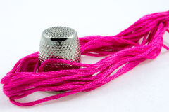 Pink cotton thread and a thimble Royalty Free Stock Images