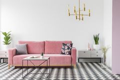 Pink couch with cushions in white apartment interior with table and plants on cabinets. Real photo stock photography
