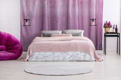 Pink coverlet on bed. Pink coverlet and patterned bedclothes on bed in female room interior with lamps, potted plant and ombre curtain Stock Photography