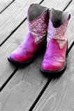 Pink Cowboy Boots for a Girl. Detail of pink cowgirl cowboy boots on wood deck for a girl royalty free stock image
