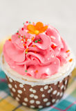 Pink cream cupcake. Pink cupcake with topping close up Stock Photos