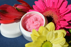 Pink cream, lips balm. A small dose with strawberry cream surrounded by flowers Royalty Free Stock Photo